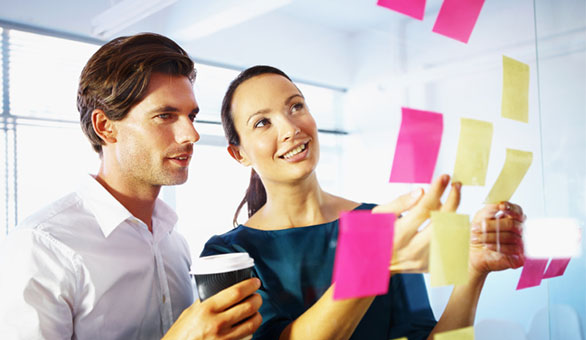 Man and Woman Brainstorming with Sticky Notes