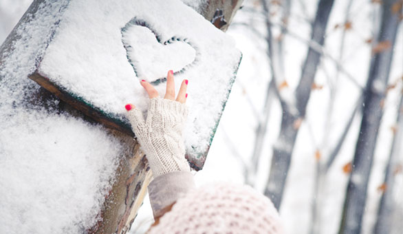 Woman Drawing Heart Into Snow